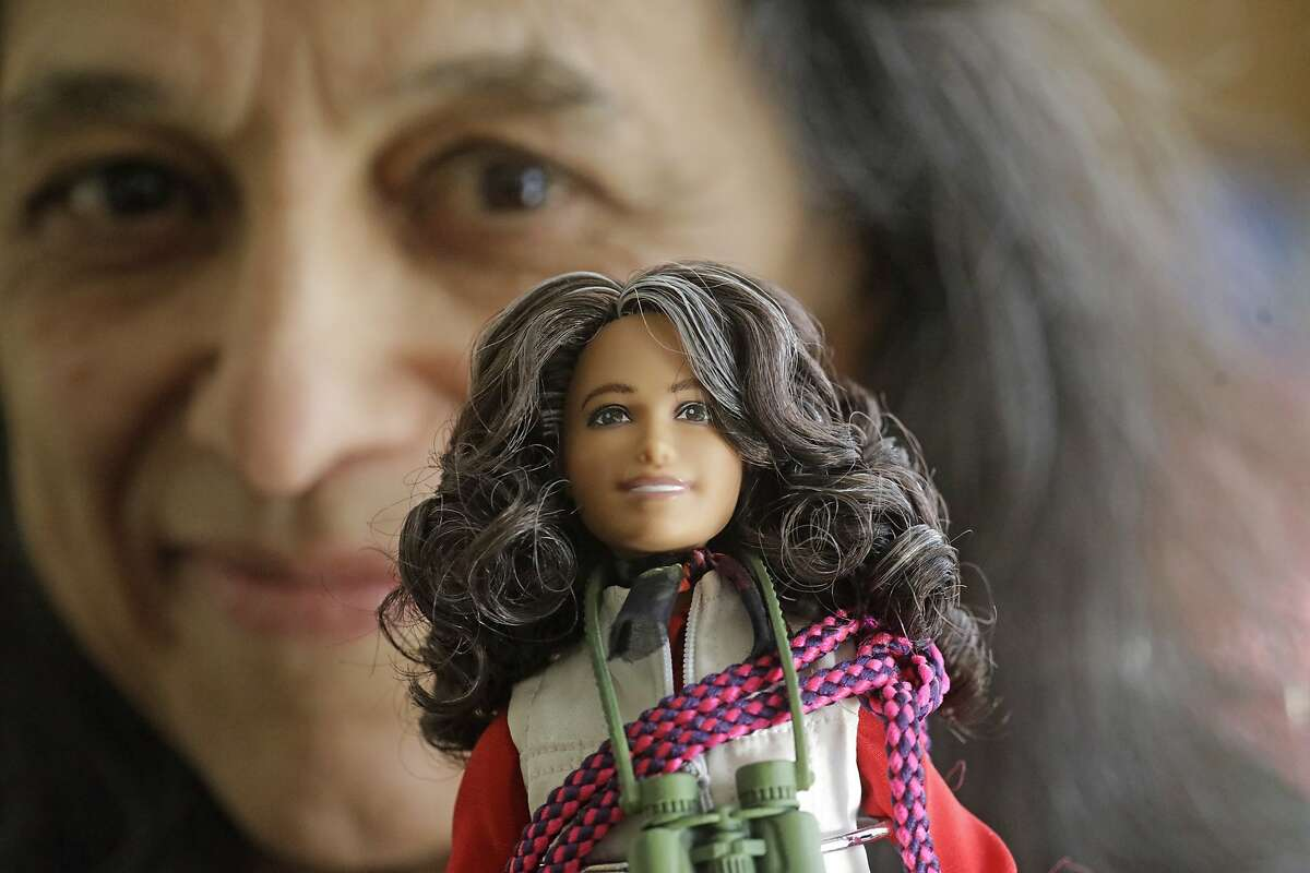 """This Dec. 3, 2019, photo, ecologist Nalini Nadkarni is shown in her lab on the University of Utah campus in Salt Lake City holding a Barbie created to look like her when she's climbing into the treetops to study the rainforest canopy. Nadkarni's childhood climbing trees shaped her career and now she's hoping she can get help kids interested in science in an new way: Barbies. Nadkarni has long created her own """"treetop Barbies"""" and has now helped Mattel and National Geographic create a line of dolls with careers in science and conservation. (AP Photo/Rick Bowmer)"""