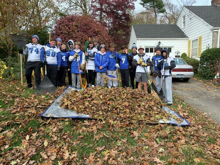 Darien's eighth grade football team raked leaves for seniors. Photo: Contributed