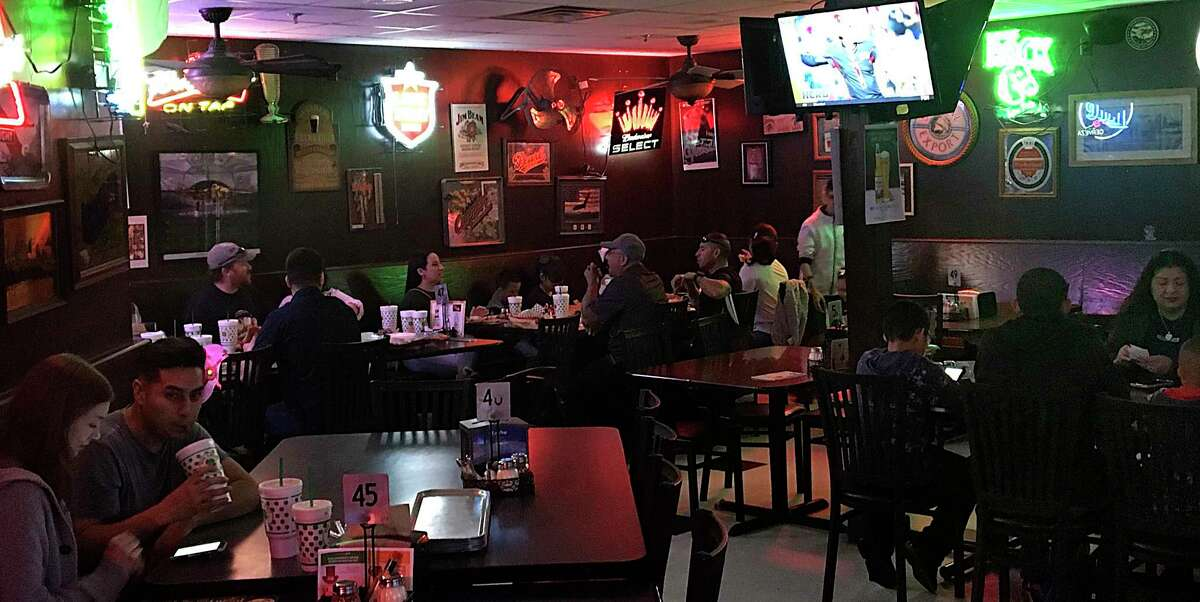 The multiple dining rooms are lit with neon signs at Big Lou's Pizza.