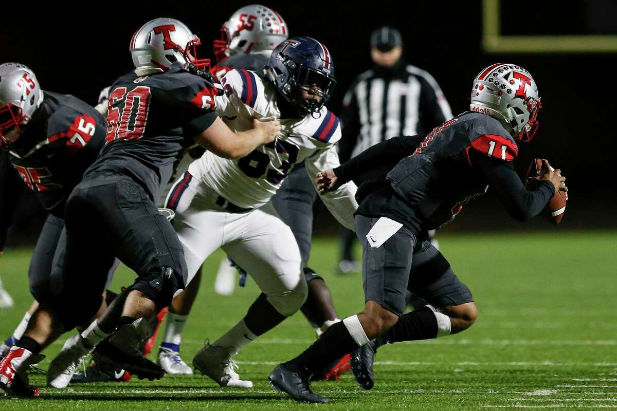 Travis Tigers Eric Rodriguez (11) scrambles under pressure by Tompkins Falcons nose guard Eti-ini Bassey (63) during the first half of the high school football playoff game between the Tompkins Falcons and the Travis Tigers at Mercer Stadium in Sugar Land, TX on Thursday, November 14, 2019. The Falcons lead the Tigers 21-14 at halftime.