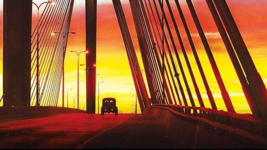 An antique vehicle travels over the Clark Bridge in Alton during sunset. Photo: John Badman | Telegraph File Photo