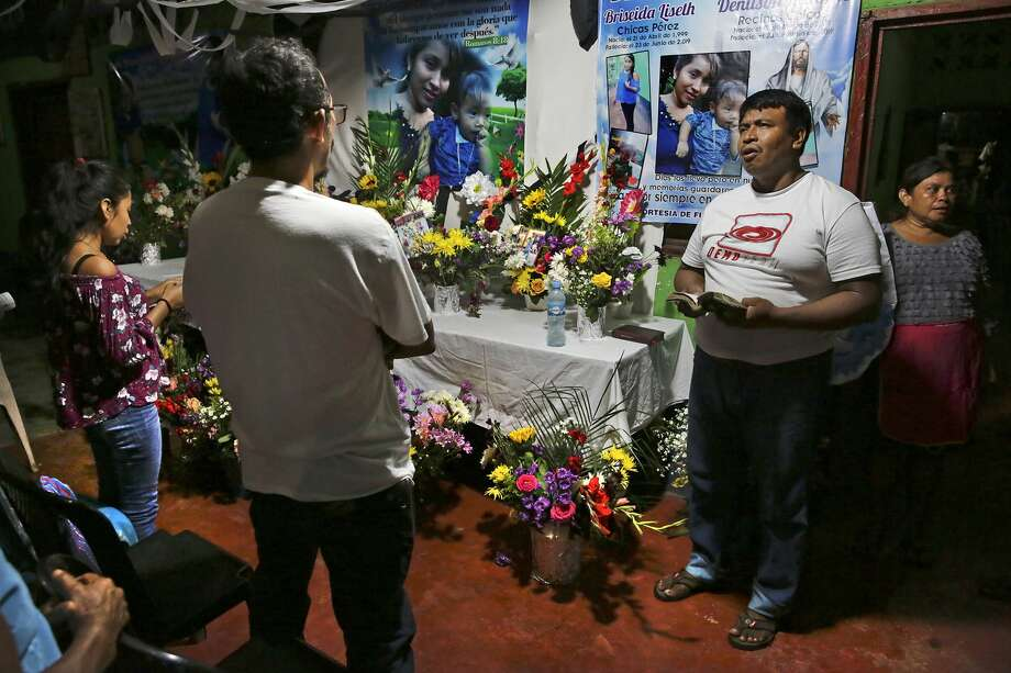 A Catholic layman Onofre Dioncio Paxtor leads a group in song in front of the shrine for Briseyda Lisseth Chicas Perez and her son Denilson, at the family's home in Chiquirines, Guatemala, on Sunday, June 30, 2019. Two other children from the nearby village of El Reparo who were traveling with Briseyda also died on the trip. Photo: Bob Owen/Staff Photographer