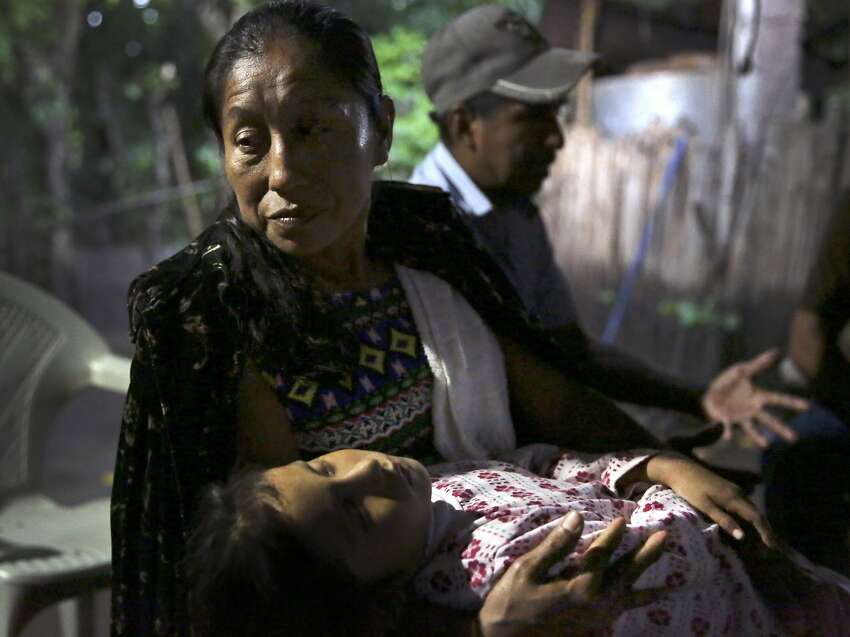Amalia Perez, center, mother of Briseyda,Lisseth Chicas Perez holds her sleeping adopted daughter who has a heart condition in their home in Chiquirines, Guatemala, on Sunday, June 30, 2019.