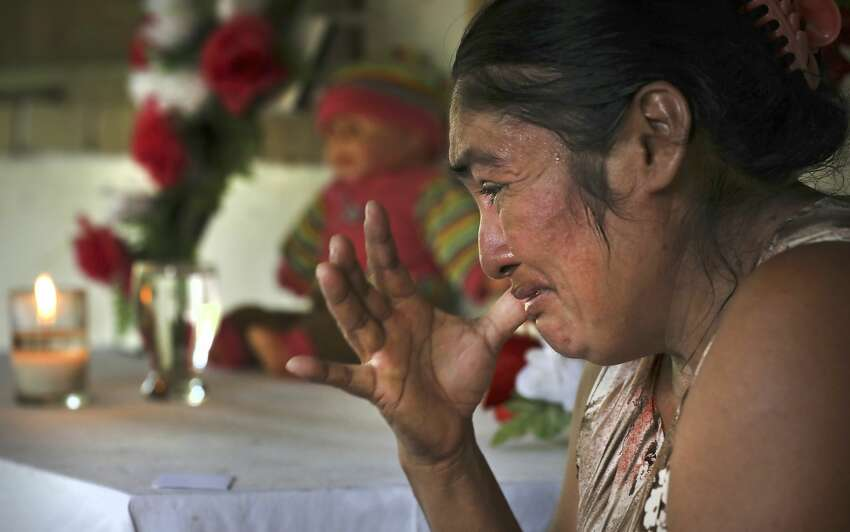 Amelia Sopon, 42, grandmother of 1-year-old Marleny Mereidy Rivera Reyes, grieves the death of her granddaughter by a small shrine at her home in El Reparo, Guatemala, on Monday July 1, 2019.