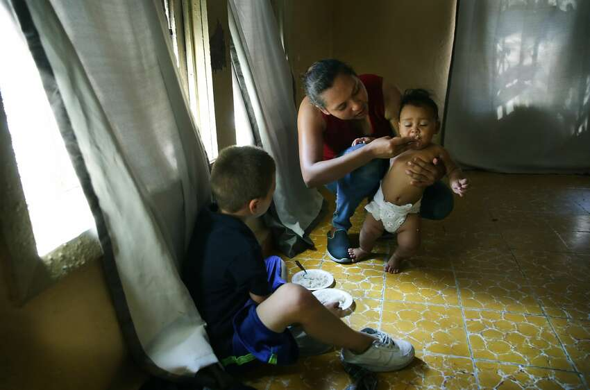 Mariluz Calderon, mother of 4 kids, from Nicaragua, feeds her youngest, Braulio, from a plate of rice in the Good Samaritan Shelter in Nuevo Laredo, Mexico. Migrants from Central America and Cuba go to asylum hearings in Laredo, Texas, on Thursday, Sept. 19, 2019.