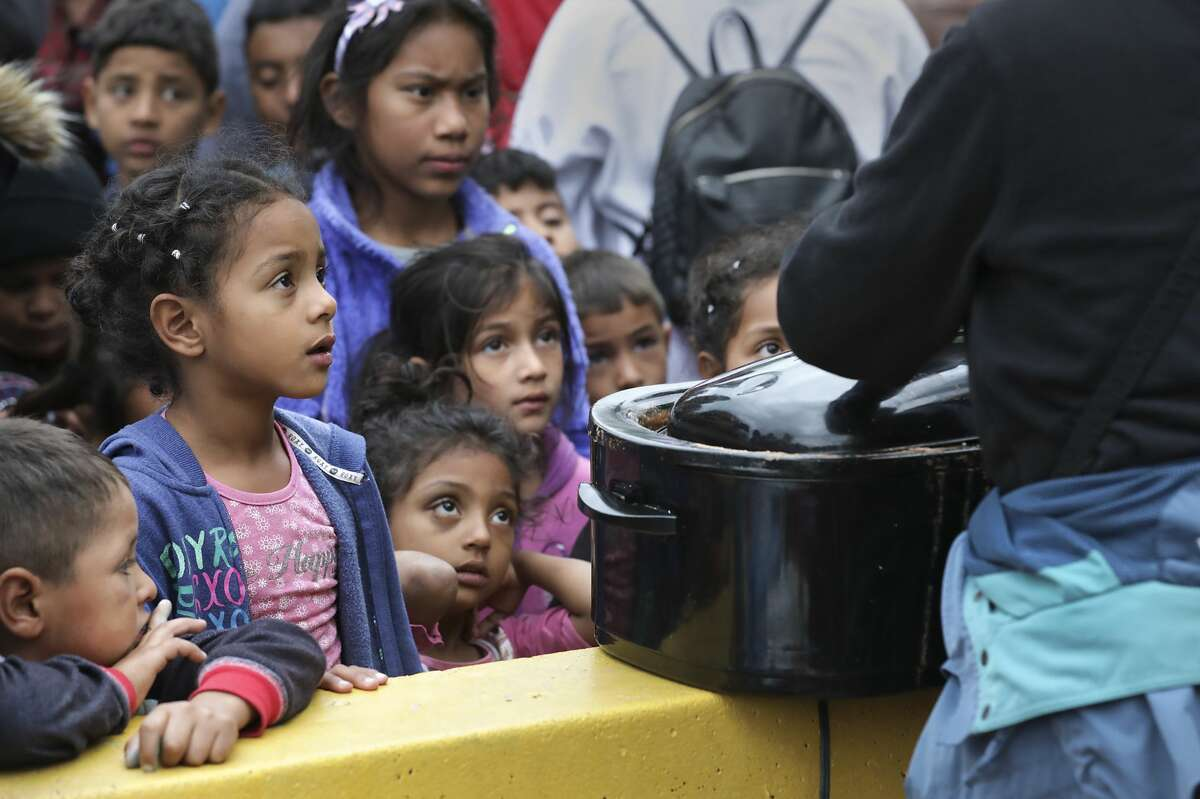 Migrant children line up in a make-shift camp at the International Bridge in Matamoros to be fed by members of Team Brownsville, a group of individuals that collect donations of food and shelter items to give to migrants waiting to apply for asylum in the U.S. on Tuesday, April 2, 2019.