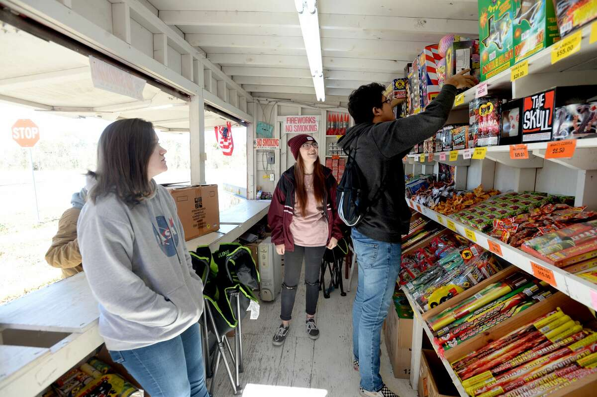 "From left, Rebecca Cates and Claudia Cannon watch as Daniel Rodriguez restocks the shelves at the fireworks stand run by Ramirez Carpet & Tile on U.S. 90.It's the second biggest time of the year for fireworks vendors as New Year's celebrants look to ring in the new year not with a bell but a boom. This year's top sellers are the ""Snow Cone"" and ""Diablo 12"" (which is available again this year). The stand will be open until midnight Wednesday morning for last-minute fireworks shoppers on New Year's Eve. Photo taken Monday, December 30, 2019 Kim Brent/The Enterprise"