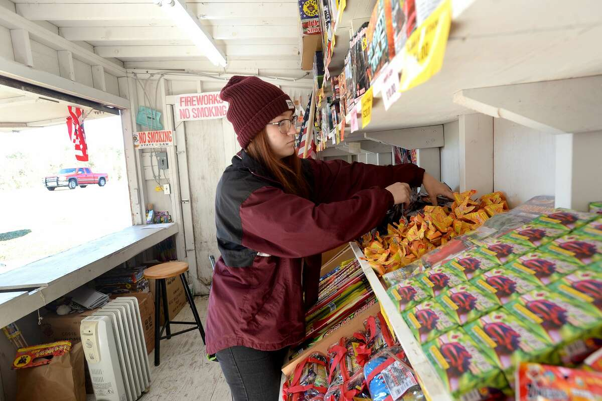 "Claudia Cannon restocks items at the fireworks stand run by Ramirez Carpet & Tile on U.S. 90.It's the second biggest time of the year for fireworks vendors as New Year's celebrants look to ring in the new year not with a bell but a boom. This year's top sellers are the ""Snow Cone"" and ""Diablo 12"" (which is available again this year). The stand will be open until midnight Wednesday morning for last-minute fireworks shoppers on New Year's Eve. Photo taken Monday, December 30, 2019 Kim Brent/The Enterprise"