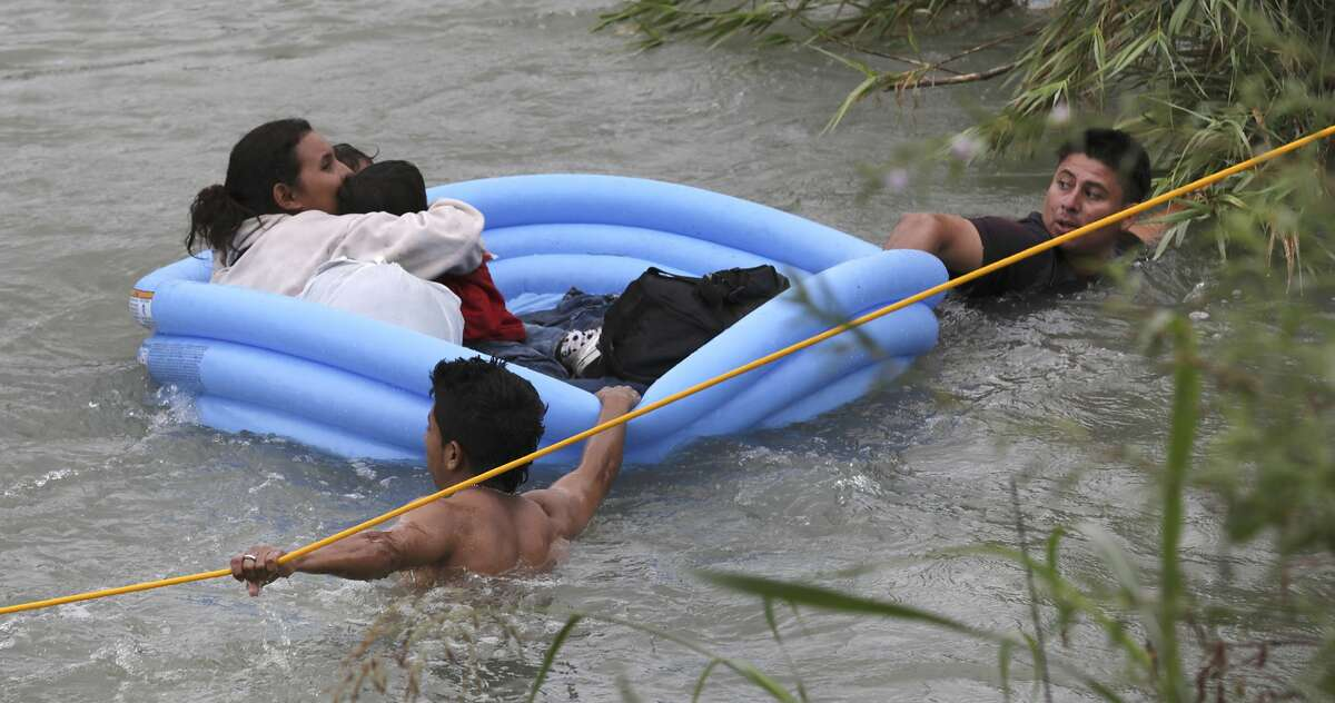A mother from Honduras clings to her two children ages 2 and 4 as her husband, right, pulls the make shift raft to shore as Border Patrol agents react to three rafts crossing the Rio Grande River in Eagle Pass, Texas, on Friday, May 10, 2019.