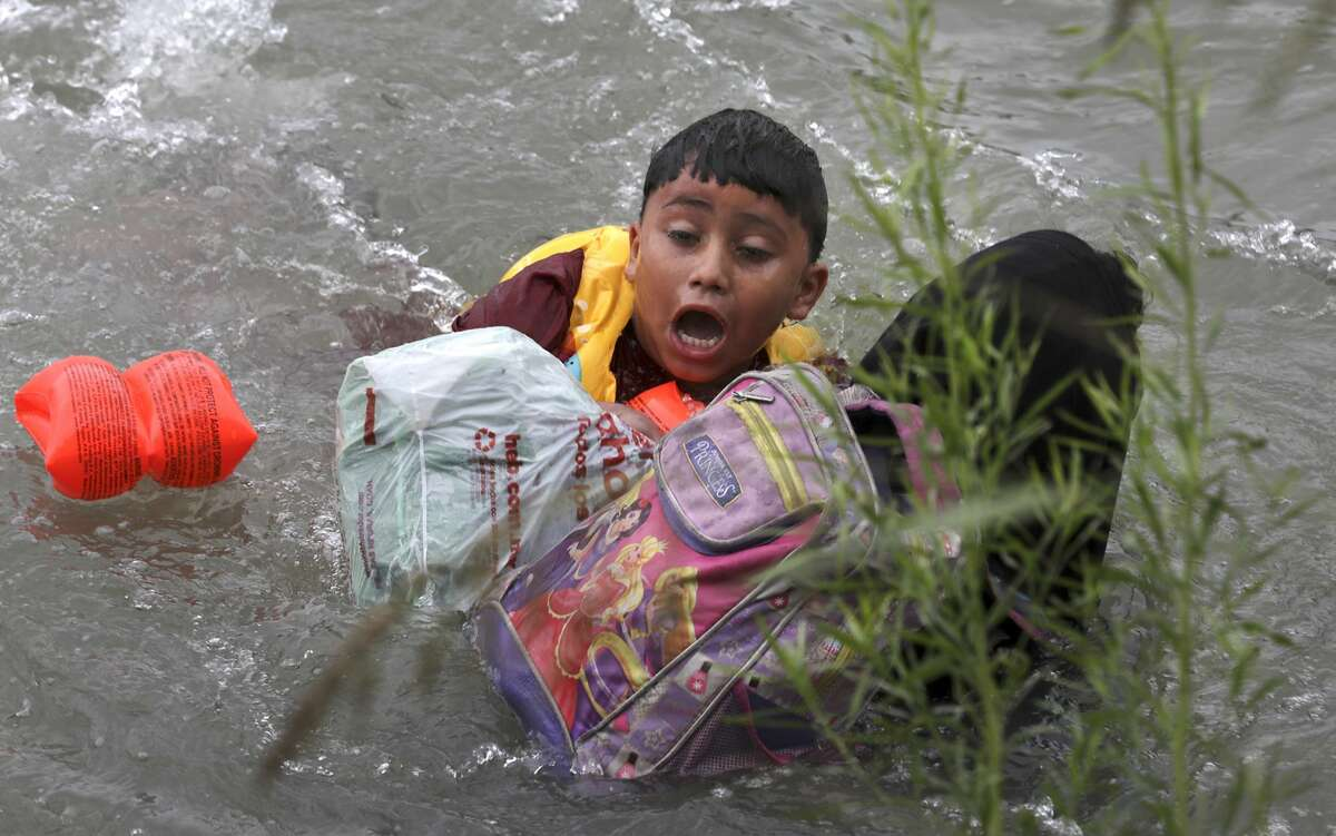 A 7-year-old boy from Honduras clings to his mother as Border Patrol agents respond to three rafts crossing the Rio Grande River in Eagle Pass, Texas, on Friday, May 10, 2019.