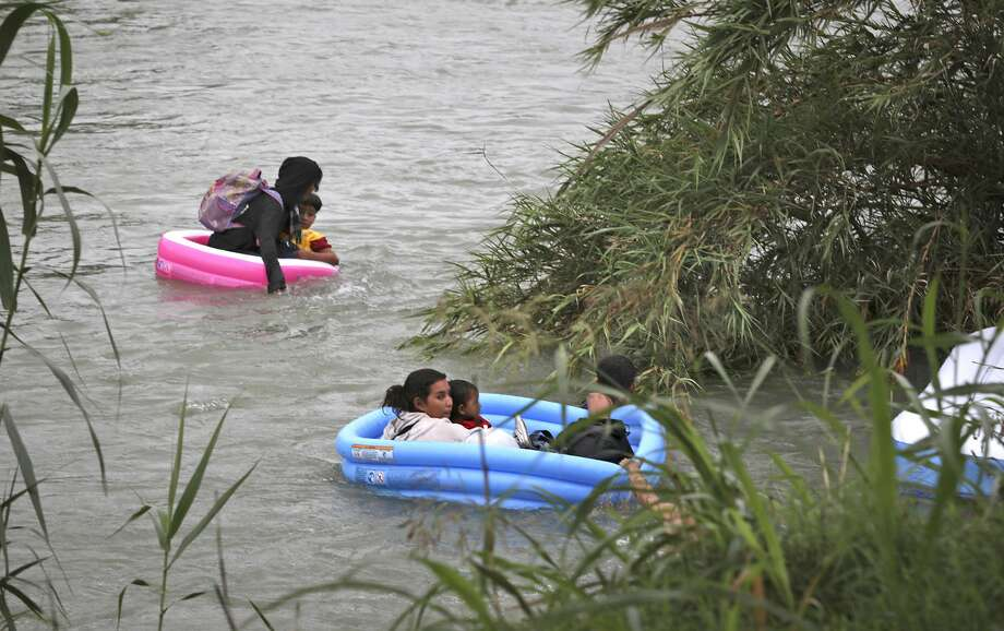 Migrants from Honduras and El Salvador cross the Rio Grande River in three inflatable kid pools used as rafts before Border Patrol Agents pull them out in Eagle Pass, Texas, on Friday, May 10, 2019. Photo: Bob Owen/Staff Photographer