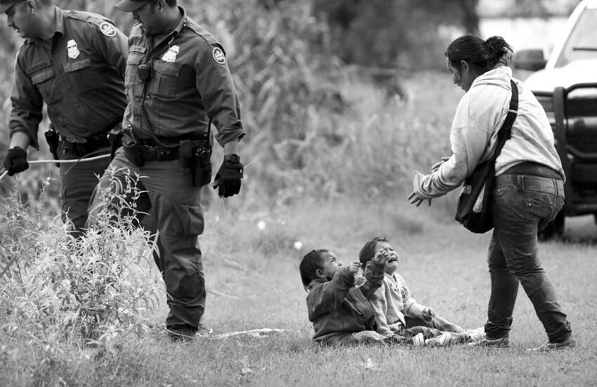 A mother from Honduras goes to her two children, two and four years old, after Border Patrol agents react to three rafts crossing the Rio Grande River in Eagle Pass, on Friday, May 10, 2019.