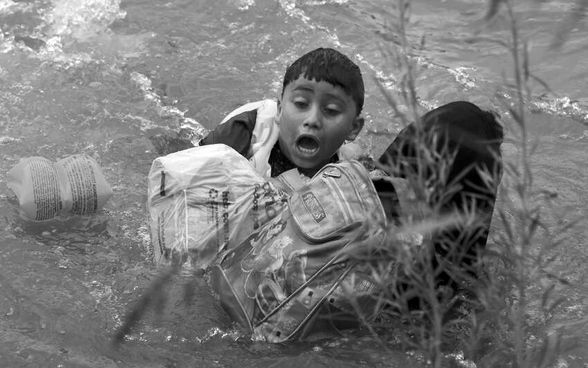 A seven year-old boy from Honduras clings to his mother as Border Patrol agents respond to three rafts crossing the Rio Grande River in Eagle Pass, on Friday, May 10, 2019.
