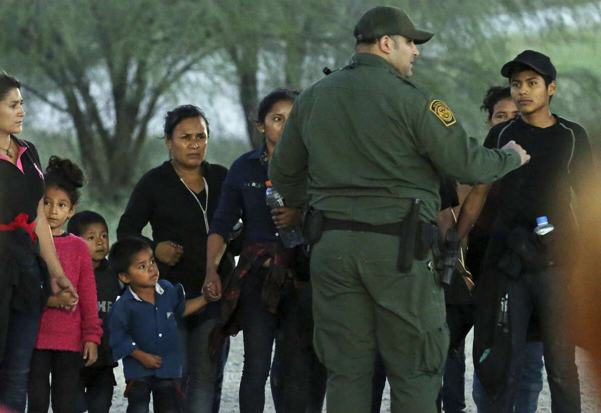 A U.S. Border Patrol agent directs a group of 13 migrants at a field tent under the Anzalduas International Bridge in Hidalgo County, Texas, Thursday, July 18, 2019. The agents were in the process of a larger group, foreground, that surrendered earlier in the morning. The family units consisted mostly of Central American migrants.
