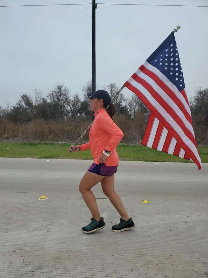 Lupita Hernandez is honoring fellow vets who have suffered from PTSD this week by running 200 miles from Houston to San Antonio, planting a roadside flag every mile in memory of a vet who has fought the disorder. Photo: Lily Hernandez