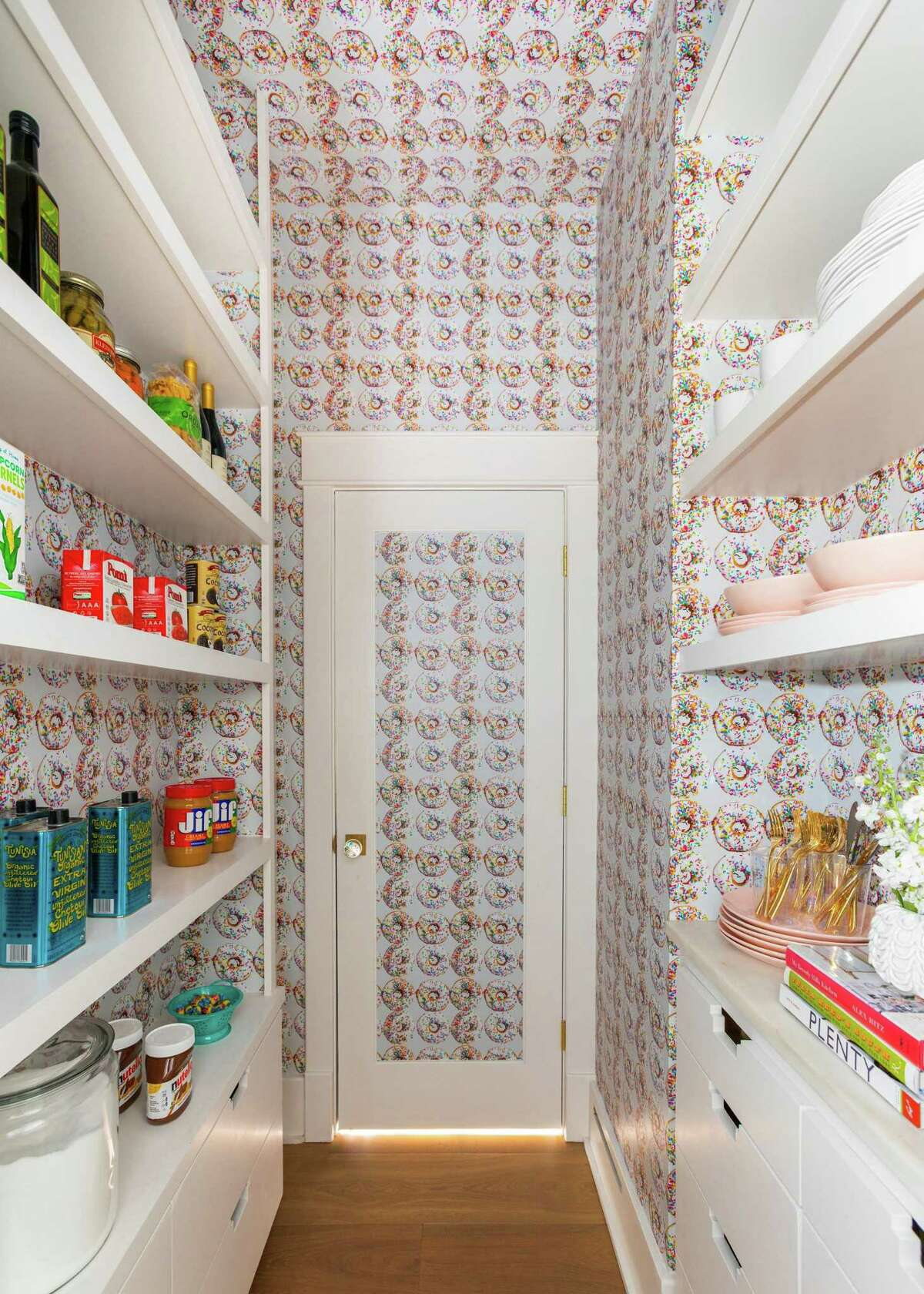 For the pantry in the home of client Julie Soefer, interior designer Courtnay Tartt Elias of Creative Tonic Design installed wallpaper of doughnuts with sprinkles. The wallpaper is custom made from a photo taken by Soefer, a professional photographer.
