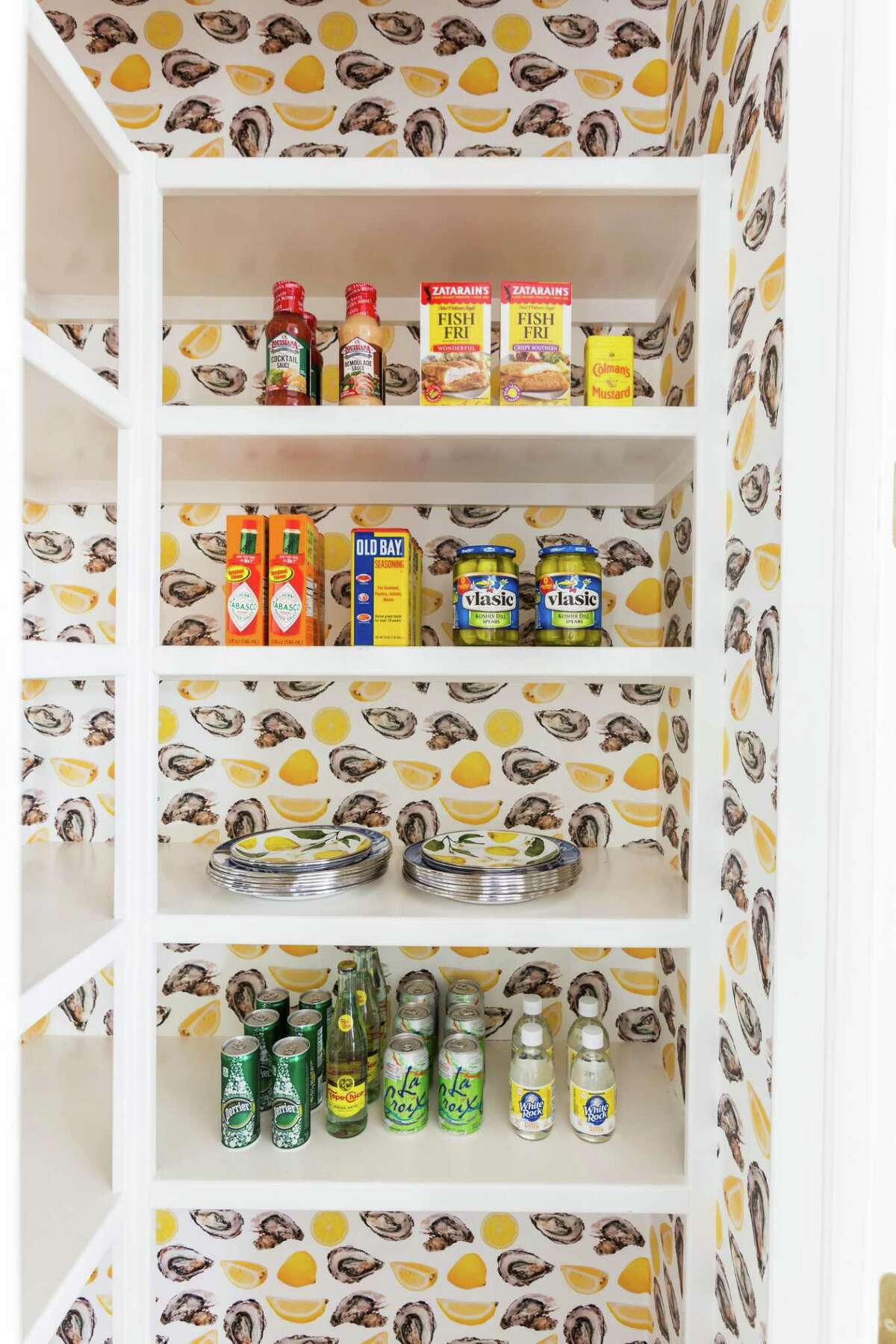 Houston interior designer Courtnay Tartt Elias installed this whimsical Katie Kime wallpaper of oysters and lemon wedges in the kitchen pantry of a client's home.