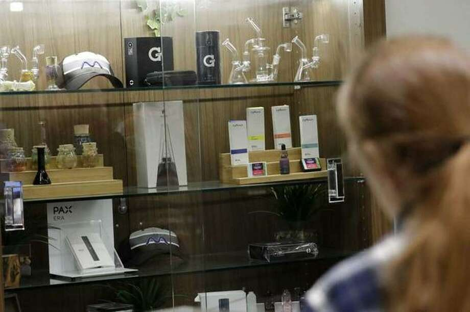 In this Thursday, Dec. 26, 2019 photo, a registered medical marijuana patient looks at products at the Rise cannabis store in Mundelein, Ill. Starting Jan. 1, 2020, Illinois will join Michigan as the only Midwestern states broadly allowing the sale and use of marijuana Photo: Photo: Nam Y. Huh, AP