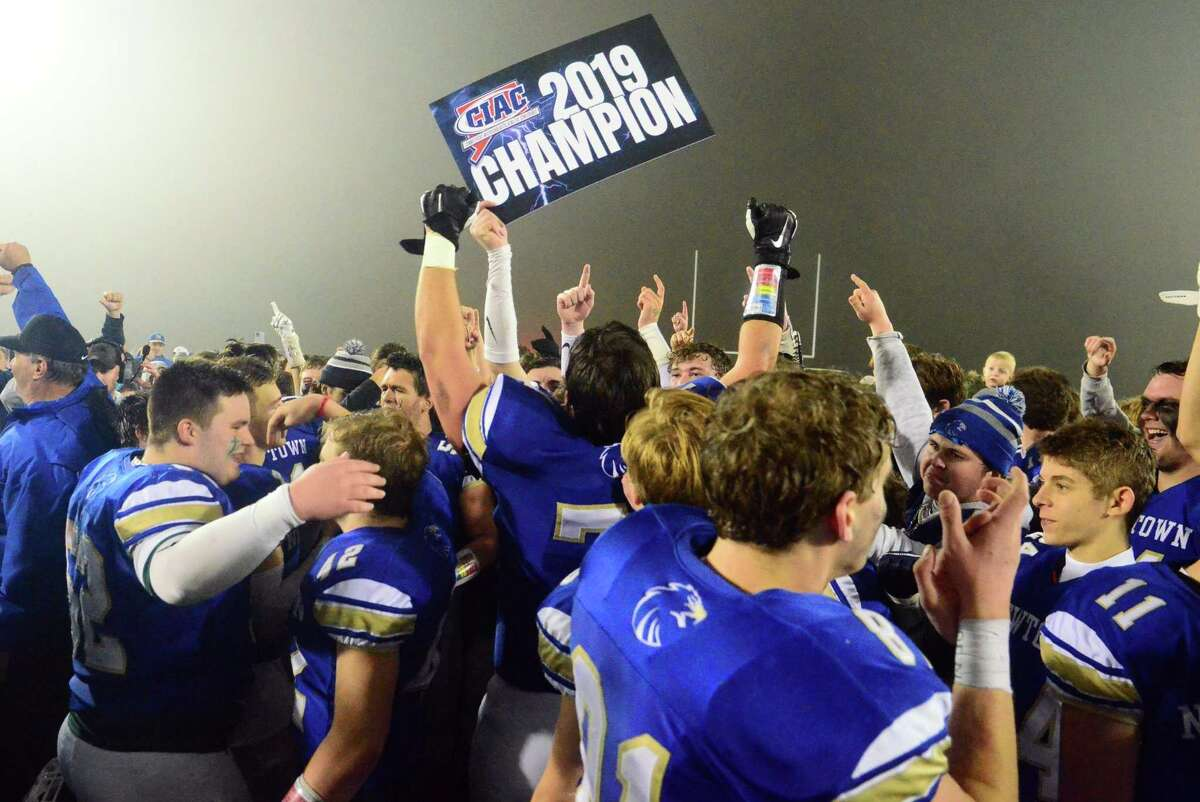 Members of the Newtown footbal team celebrate their dramatic win in the Class LL championship game against Darien.