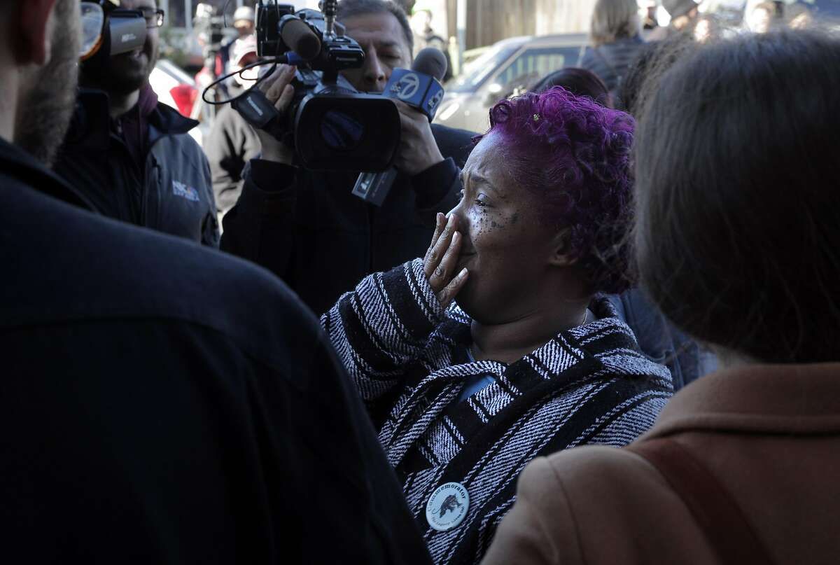 Sharena Thomas gets emotional at seeing all the support she has from a human blockade at a home on Magnolia Street in Oakland, Calif., after a judge ordered a continuance to a case involving several mothers with children living in an empty home owned by Wedgewood Properties, a Redondo Beach company, on Monday, December 30, 2019. Dominique Walker, a mother to a 1-year-old, moved into a vacant home on Nov. 18 with another Oakland mother, and earlier this month, the corporation that owns the home, delivered an eviction notice. The women - who are homeless - first took over the residence to get shelter and to bring attention to how vacant properties in Oakland are contributing to the homeless crisis.