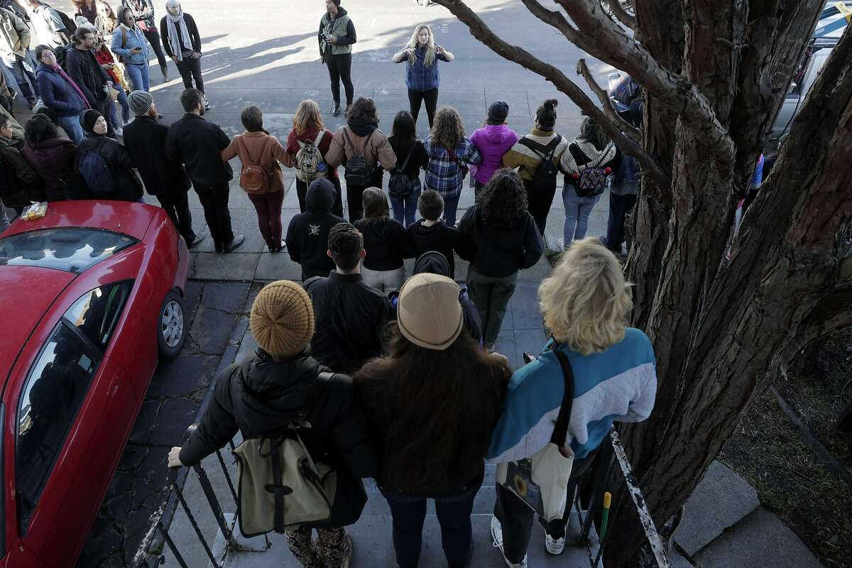 Nicole Deane, with Moms for Housing Solidarity Committee, speaks to supporters forming a human blockade at a home on Magnolia Street in Oakland, Calif., on Monday, December 30, 2019. A judge ordered a continuance to a case involving several mothers with children living in an empty home owned by Wedgewood Properties, a Redondo Beach company, Dominique Walker, a mother to a 1-year-old, moved into a vacant home on Nov. 18 with another Oakland mother, and earlier this month, the corporation that owns the home, delivered an eviction notice. The women - who are homeless - first took over the residence to get shelter and to bring attention to how vacant properties in Oakland are contributing to the homeless crisis.