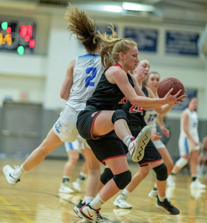 New Canaan's Jane Charlton comes down with a rebound in front of Darien's Aerin Bowman (2) during a girls basketball game between the rivals at Darien High School on Monday, Dec. 30, 2019. Photo: Mark Maybell / Darien Athletic Foundation / Contributed / (c) Mark Maybell/Darien Athletic Foundation
