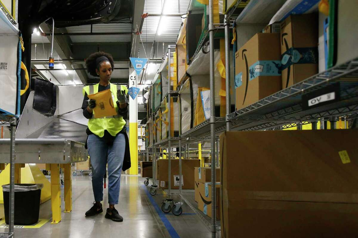 In this Dec. 17, 2019, photo Tahsha Sydnor stows packages into special containers after Amazon robots deliver separated packages by zip code at an Amazon warehouse facility in Goodyear, Ariz. Amazon and its rivals are increasingly requiring warehouse employees to get used to working with robots. The company now has more than 200,000 robotic vehicles it calls a€œdrivesa€ that are moving goods through its delivery-fulfillment centers around the U.S. (AP Photo/Ross D. Franklin)