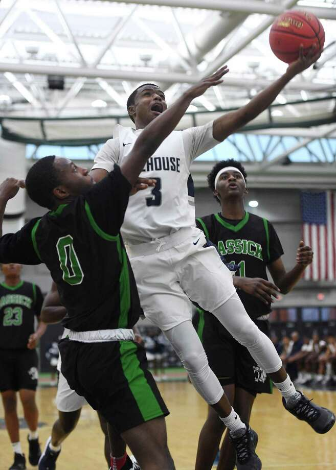 Hillhouse's Tazhon Daniels drives to the hoop while being defended by Bassick's Jermaine Grant in the first half on Monday. Photo: Brian A. Pounds / Hearst Connecticut Media / Connecticut Post