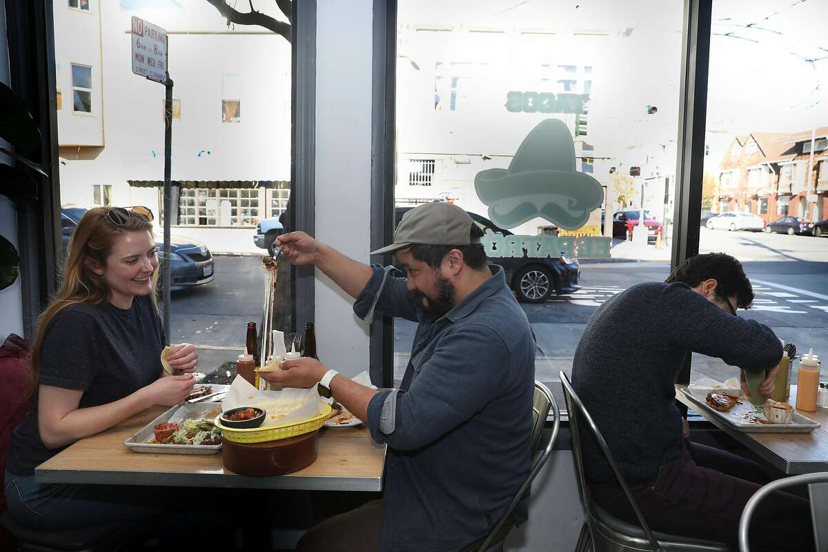 Lesley Scott (left) watches as Peter Mosquedo has a choriqueso at Tacos El Patron on S. Van Ness Ave. on Monday, Dec. 30, 2019, in San Francisco, Calif.