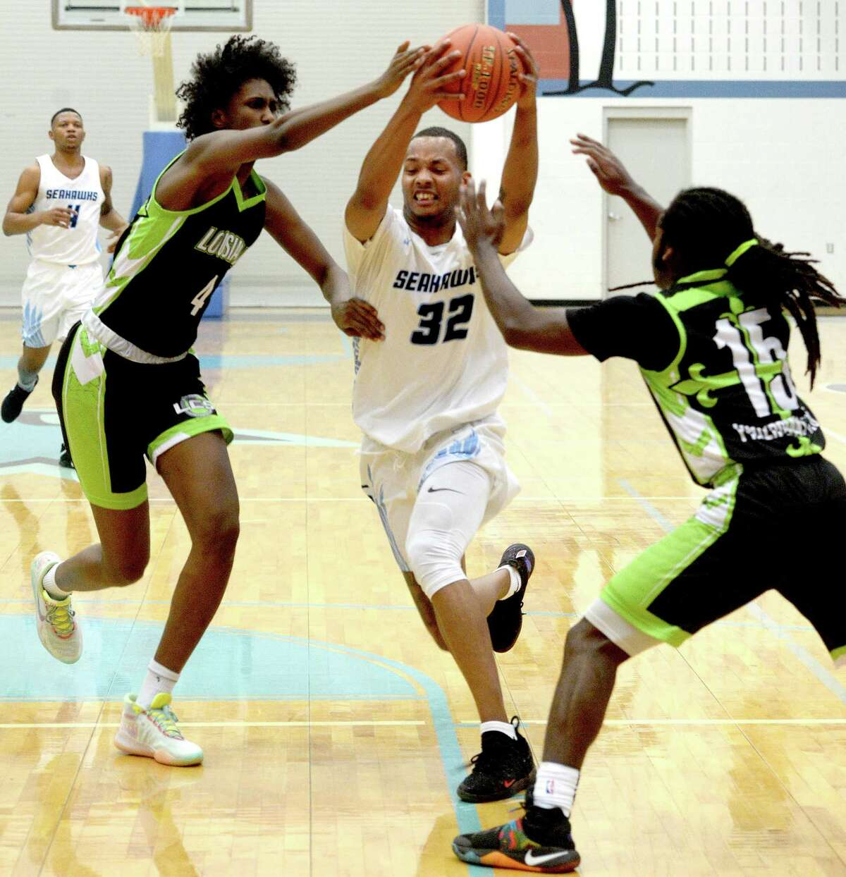 Lamar State College Port Arthur's J'Son Brooks battles to get inbetween pressure from Louisiana Christian Prep's Abdalla Mohamed and Xavier Smith during the Seahawk's New Year's Classic opening game Monday. Photo taken Monday, December 30, 2019 Kim Brent/The Enterprise