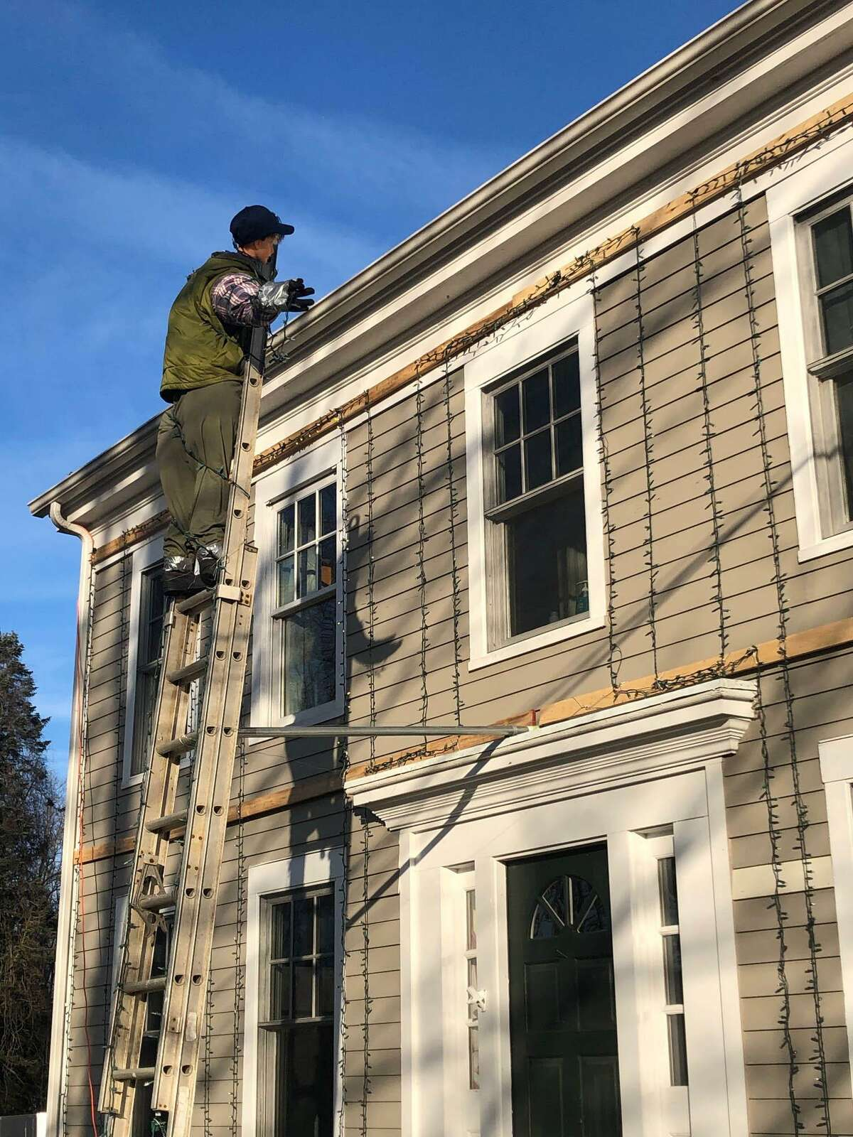 A mannequin of Clark Griswold, the main character in the film, hangs Christmas lights on the Clark family home in New Milford.