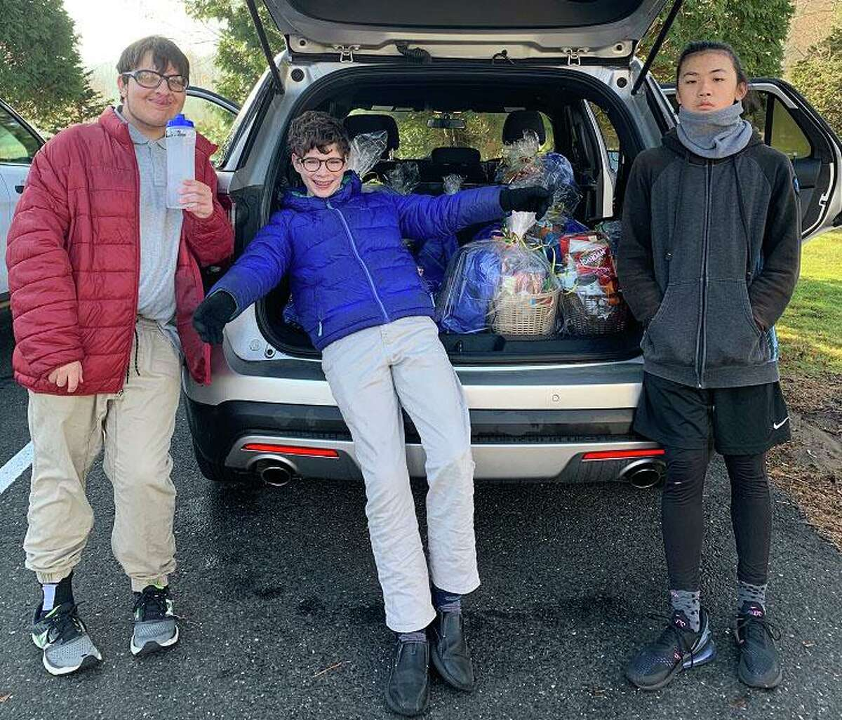 Students from the Glenholme School in Washington recently prepared and delivered Thanksgiving baskets to the Northwest Connecticut Visiting Nurse Association for distribution to local families in need. The baskets were packaged by students and filled with non-perishable food donations from Glenholme staff. The school provided 12 baskets this year, each to be delivered by the VNA. Above, students Ian C., Paul M. and James T. load the car with the baskets. The Glenholme School is a therapeutic boarding and day school for students ages 10-21 with various learning, social and emotional differences.
