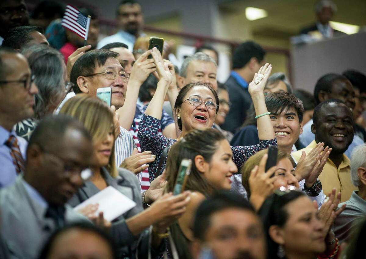 New citizens cheer after taking the formal oath of allegiance to become naturalized United States citizens during a ceremony at the M.O. Campbell Education Center in Houston, Wednesday, July 10, 2019. 2,382 new citizens wore sworn in during the ceremony. The League of Women Voters registered 2,109 of the participants to vote.