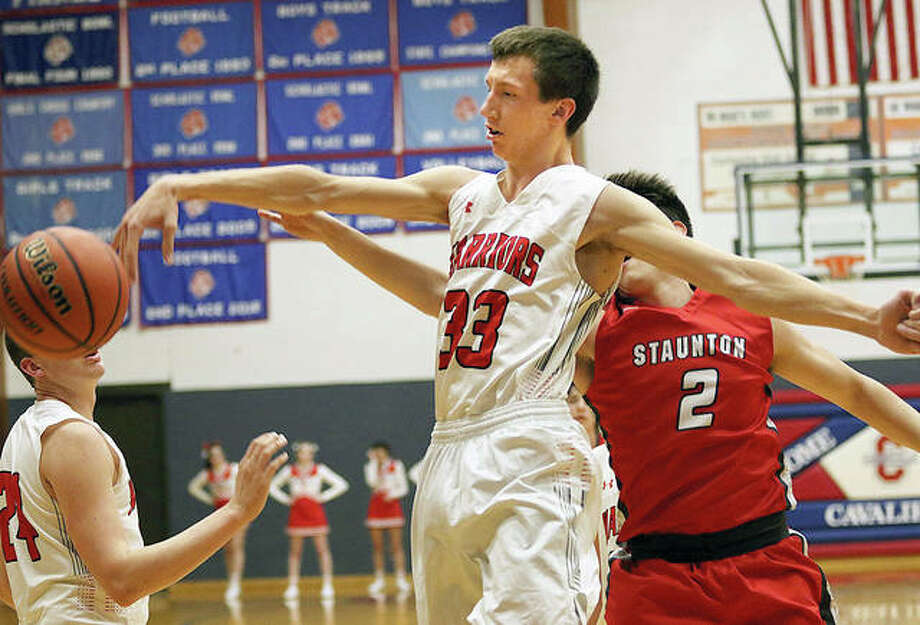 Calhoun's Corey Nelson (33) swats away a shot by Staunton's Kyle McCalla (2) in the first half Monday night in the championship game of the 54th annual Carlinville Holiday Tournament. Photo: Greg Shashack | The Telegraph