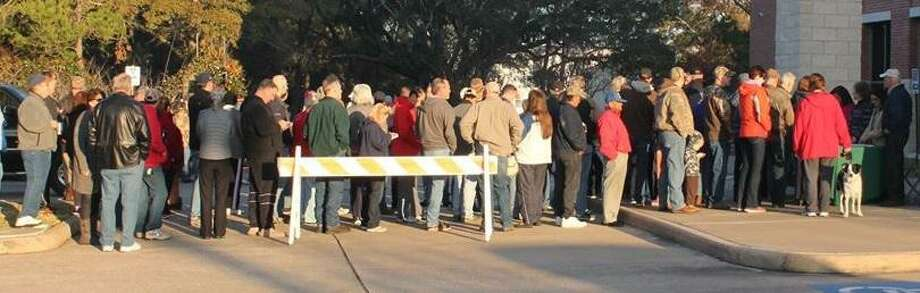 A line of people and a dog wait for the signal at a last year's tree giveaway by Keep Friendswood Beautiful.