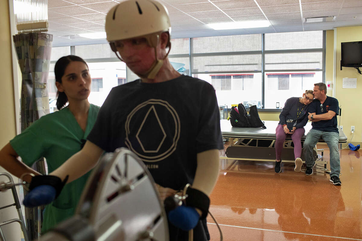DJ Sutterfield and Karl Sutterfield wait as their son, Zachary Sutterfield, exercises with physical therapist Sarah Flores, left, during his daily rehabilitation session at the U.S. Army Institute of Surgical Research Burn Center on Feb. 13, 2019.