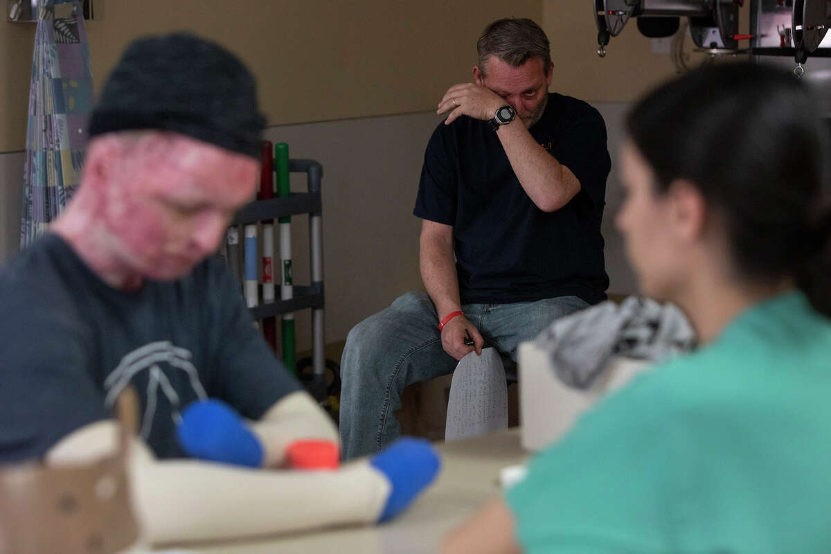 Karl Sutterfield wipes tears away after reading a letter his son, Zachary Sutterfield, left, wrote to him moments earlier as part of Zachary's daily physical therapy session at the U.S. Army Institute of Surgical Research Burn Center on Feb. 13, 2019. At right is physical therapist Sarah Flores.