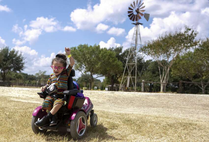 Sammi Haney, 9, cheers as she makes it down a small hill in her power chair during a homeschool day outing at Devine Acres Farm in Devine, Texas, Oct. 2, 2019. Sammi plays a supporting role in the new Netflix series Ã?'Raising Dion,Ã?