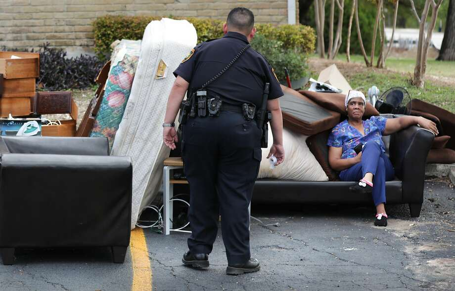 """The following photos are from """"Kicked Out,"""" the Express-News investigation about evictions in San Antonio. Bexar County Deputy Constable Edward Prado of Precinct 4, center, checks on Patricia A. White as she sits with her possessions after Prado served a writ of possession to White at Brooks Townhomes on Wednesday, Nov. 6, 2019. Photo: Bob Owen/San Antonio Express-News"""