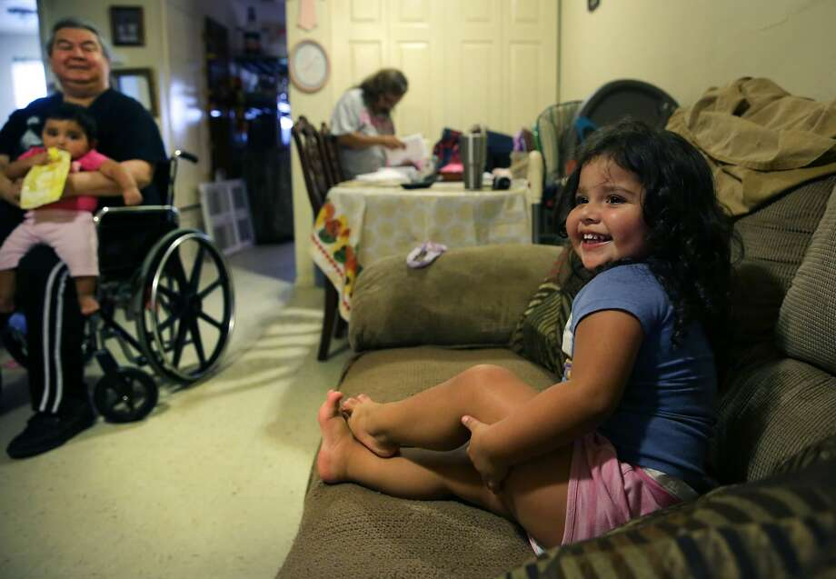 Joe Garcia, left, holds his granddaughter Ashley as his other granddaughter Izabella, 3, sits on the sofa. Joe and his wife Teresa Garcia are raising their grandchildren in their apartment, but they were almost evicted this summer. Photo: BOB OWEN/Staff Photographer