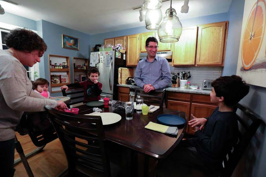 The Racco family prepares to eat dinner in their West Hartford home. Photo: Carl Jordan Castro / C-Hit.org