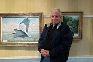 Darien resident Steve Fritsch standing near his artwork at the Atria Darien.