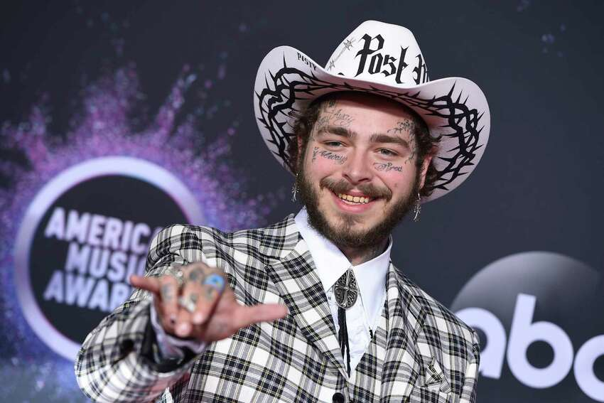FILE - In this Nov. 24, 2019, file photo Post Malone arrives at the American Music Awards at the Microsoft Theater in Los Angeles. The rap-pop star will perform at