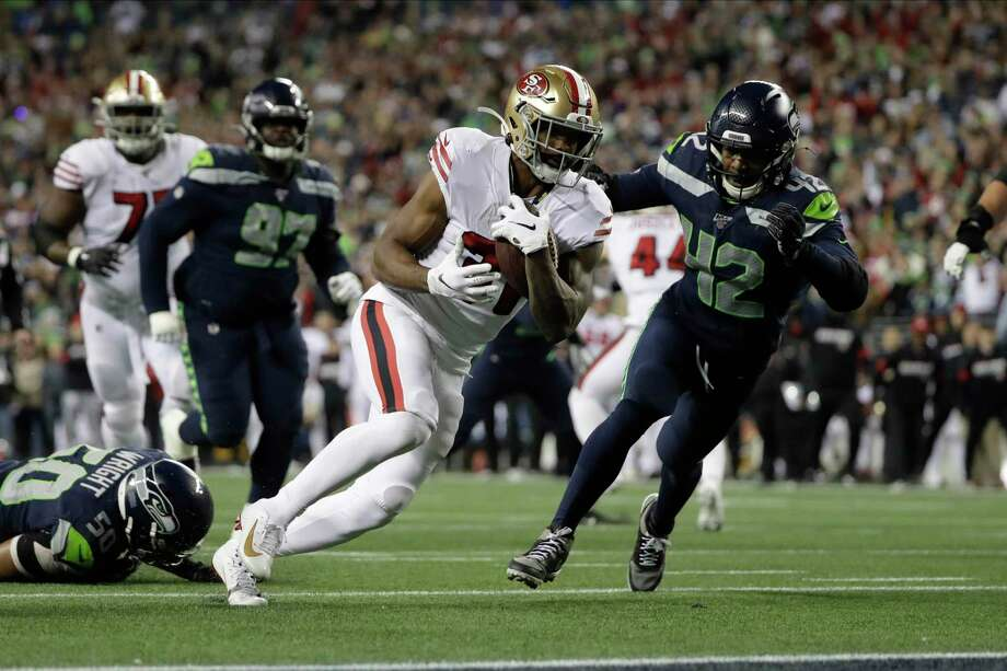 San Francisco 49ers running back Raheem Mostert, center, heads to the end zone to score against the Seattle Seahawks during the second half of an NFL football game, Sunday, Dec. 29, 2019, in Seattle. An average of 23.3 million viewers watched the game, which was shown on NBC. Photo: Ted S. Warren / Associated Press / Copyright 2019 The Associated Press. All rights reserved.