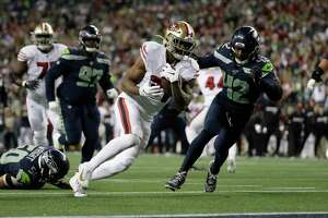 San Francisco 49ers running back Raheem Mostert, center, heads to the end zone to score against the Seattle Seahawks during the second half of an NFL football game, Sunday, Dec. 29, 2019, in Seattle. An average of 23.3 million viewers watched the game, which was shown on NBC.