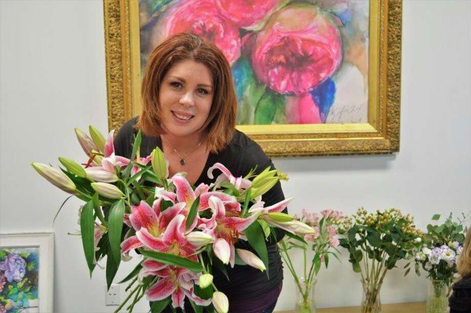 Hannah Tiffin, owner of Hannah's Flowers in Midland, poses with some lilies at her shop, located at 1531 Washington St. (Ashley Schafer/Ashley Schafer@hearstnp.com)
