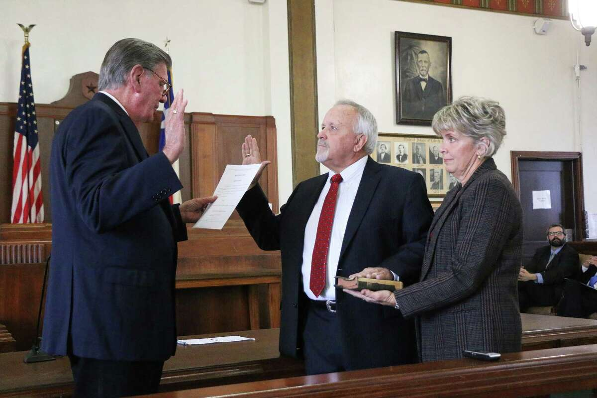 County Judge Jay Knight lays his hand on top of his grandmother's Bible being held by his wife Jan. The Bible was her last one and dates back to the 1950s. Inside is a photo of Knight's uncle, W. P.