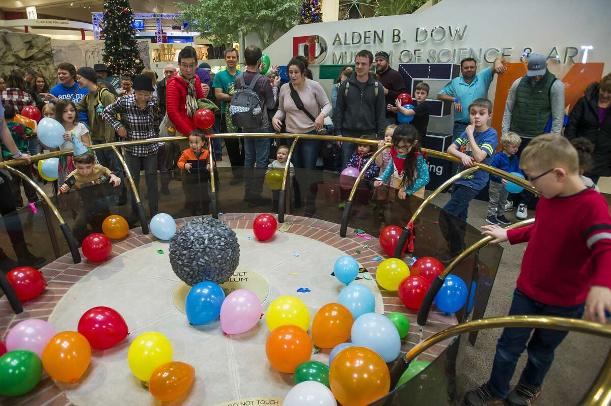 Children collect balloons during a New Year's Eve balloon drop at the Midland Center for the Arts Tuesday, Dec. 31, 2019. (Katy Kildee/kkildee@mdn.net)