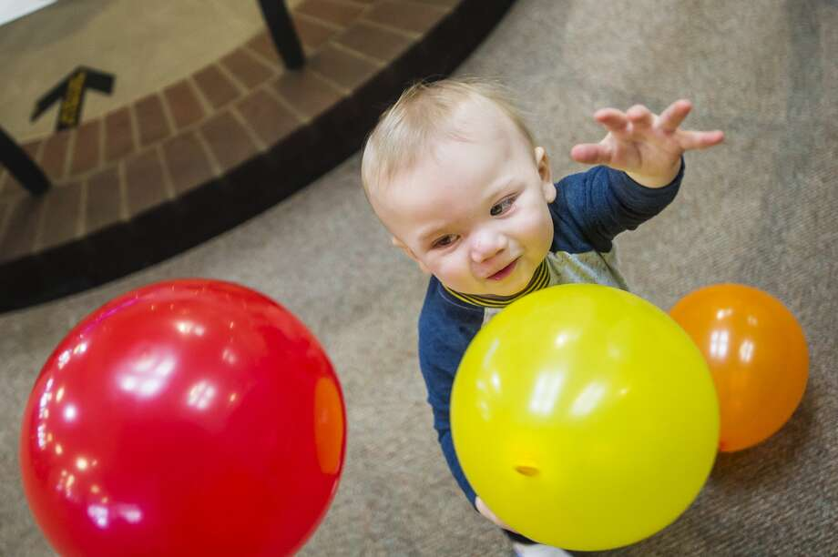 Adler Solinski, 1, catches balloons in the air during a New Year's Eve balloon drop at the Midland Center for the Arts Tuesday, Dec. 31, 2019. (Katy Kildee/kkildee@mdn.net) Photo: (Katy Kildee/kkildee@mdn.net)