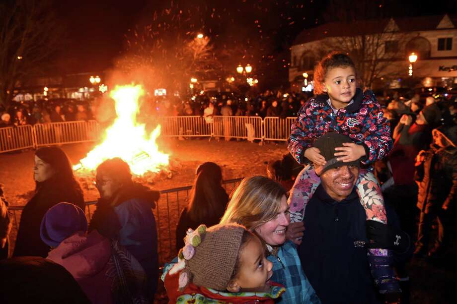 The Tarry family of Branford spent time in front of the bonfire during First Night festivities on the Branford Green on January 4, 2019. Left to right, Shelby Tarry, 6, her mother, Wendy, father, Victor, and sister, Danielle, 4. Photo: Arnold Gold / Hearst Connecticut Media / New Haven Register